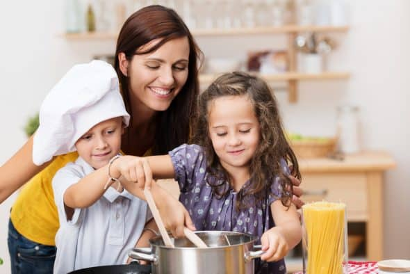 Mom cooking pasta with kids