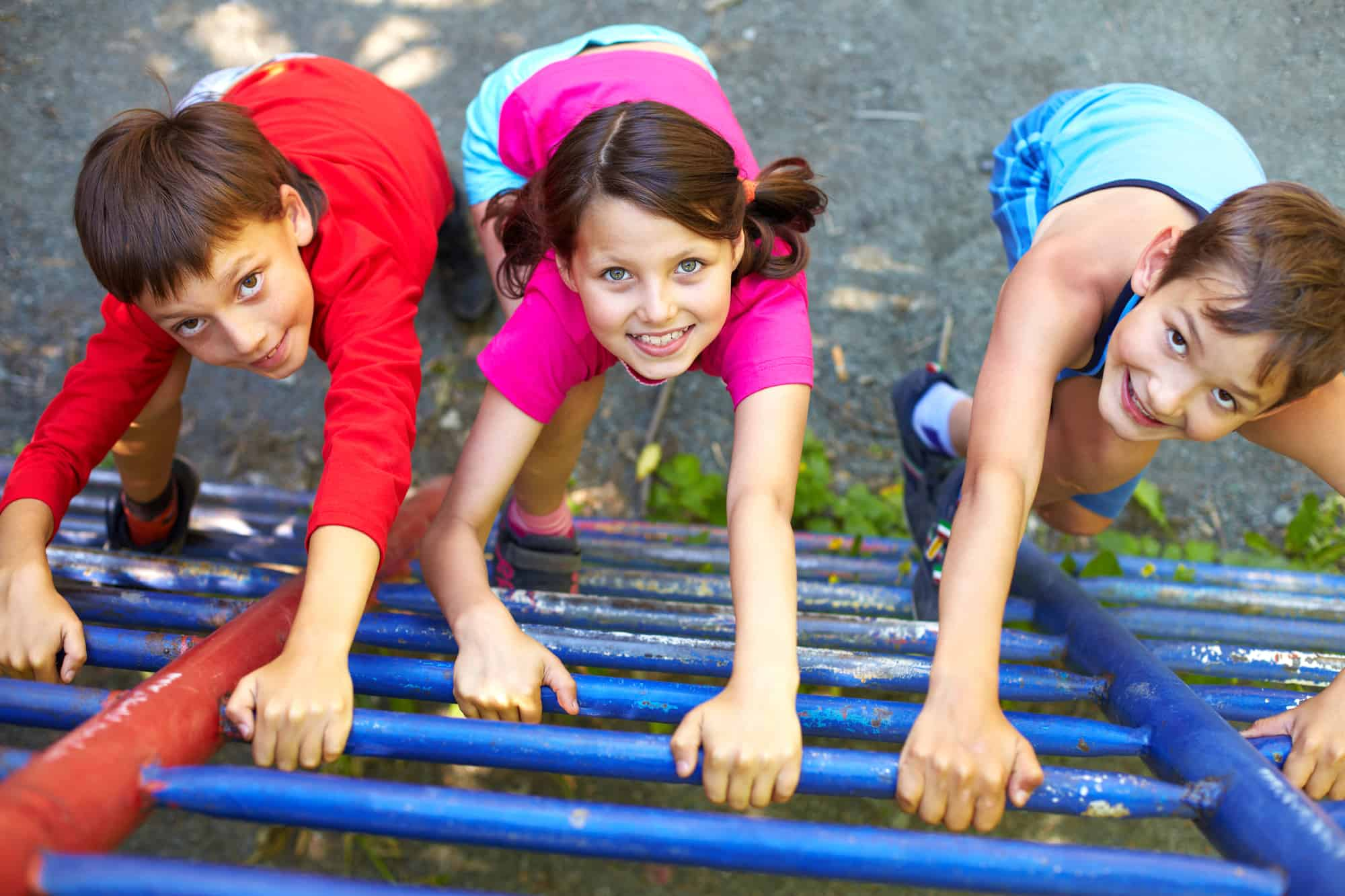 Three kids climbing a ladder at a playground