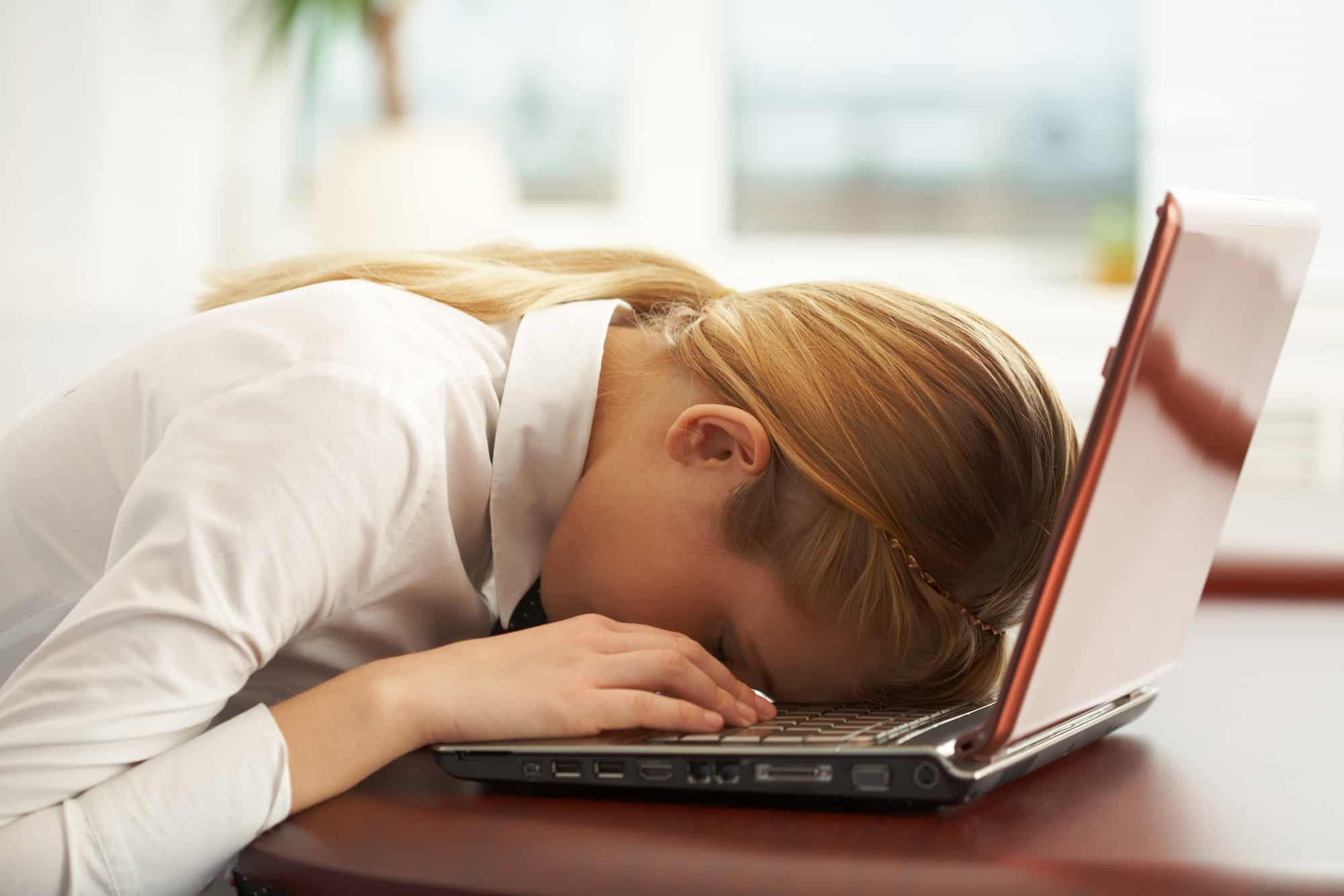 Exhausted woman with head on laptop
