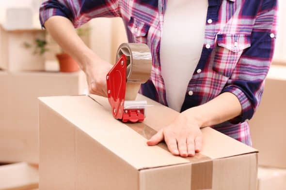 Woman packing boxes with tape