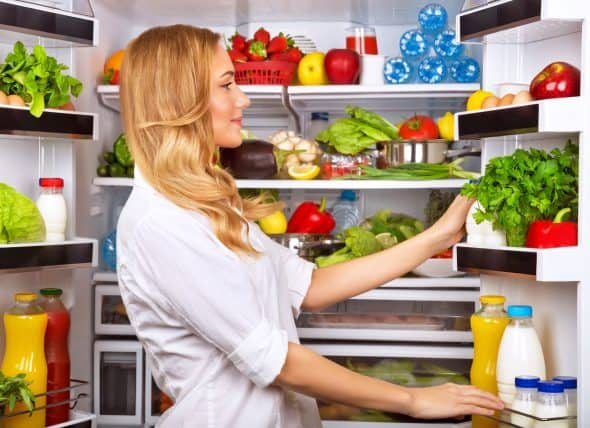 woman-looking-into-refrigerator-full-of-produce