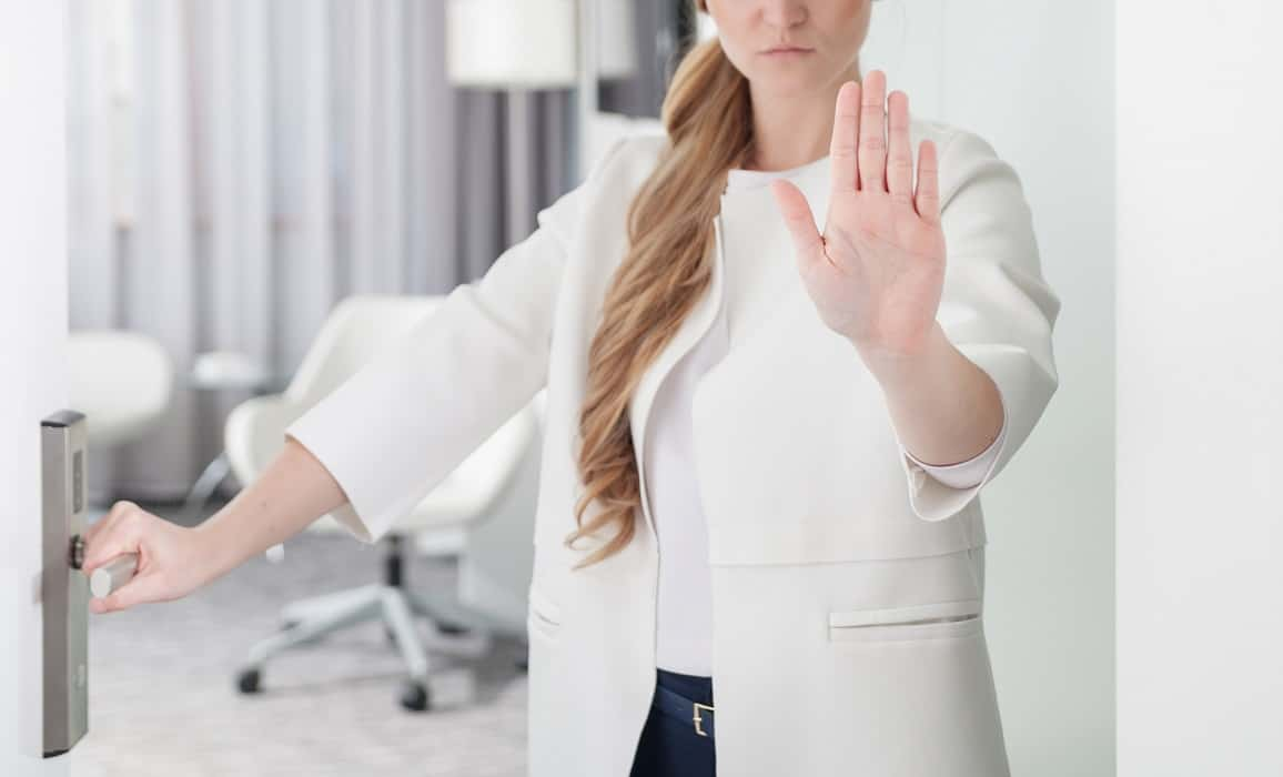 woman blocking entry with stop hand signal