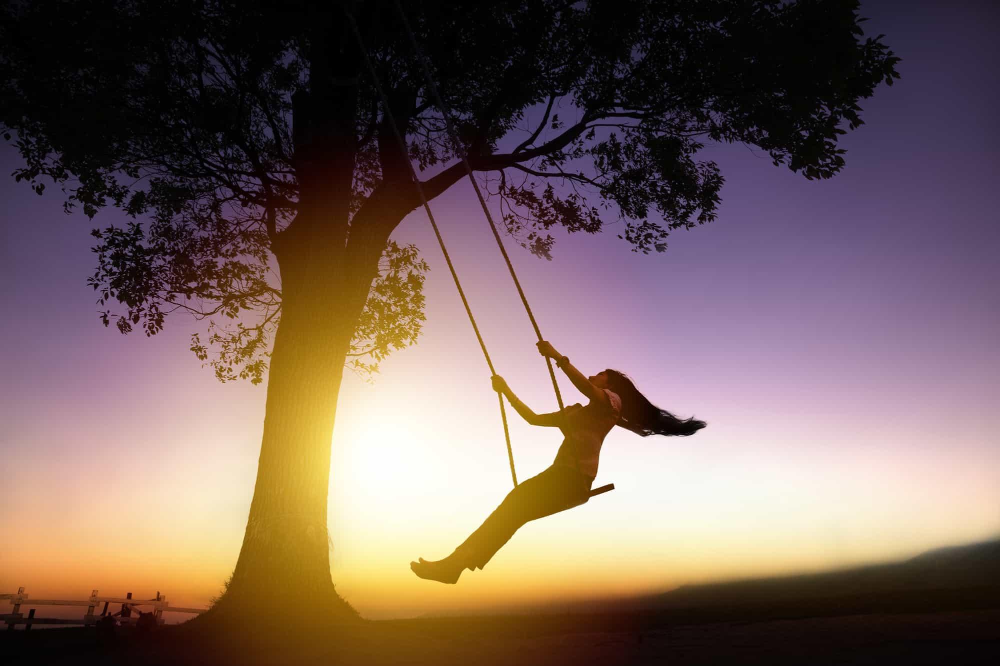 woman on swing in silhouette