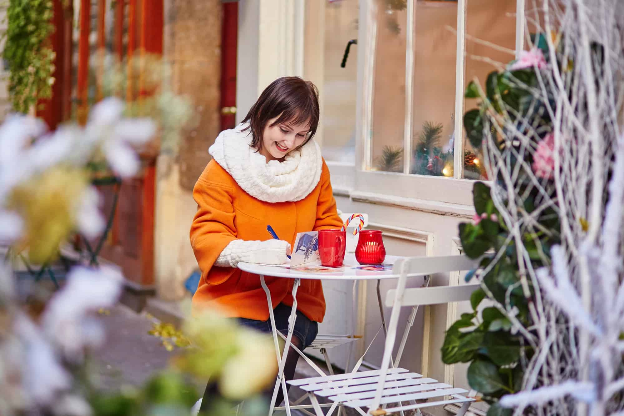 Cheerful girl writing Christmas cards in cafe