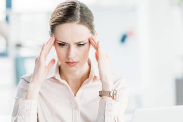 Tired pensive businesswoman with hands on head looking down