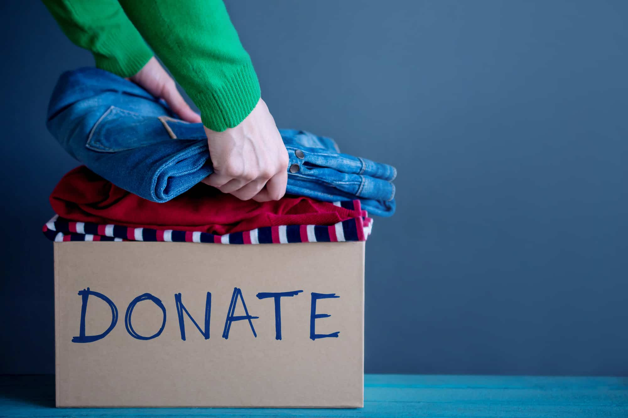 Donation Concept - Woman Preparing her Used Old Clothes into a Donate Box