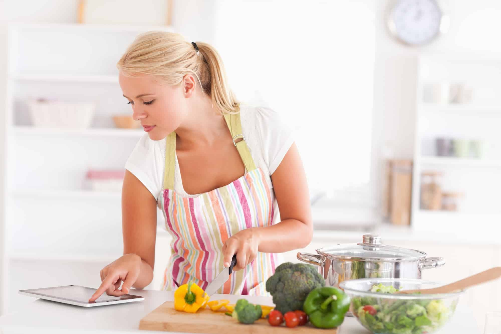 Woman cooking while looking at tablet