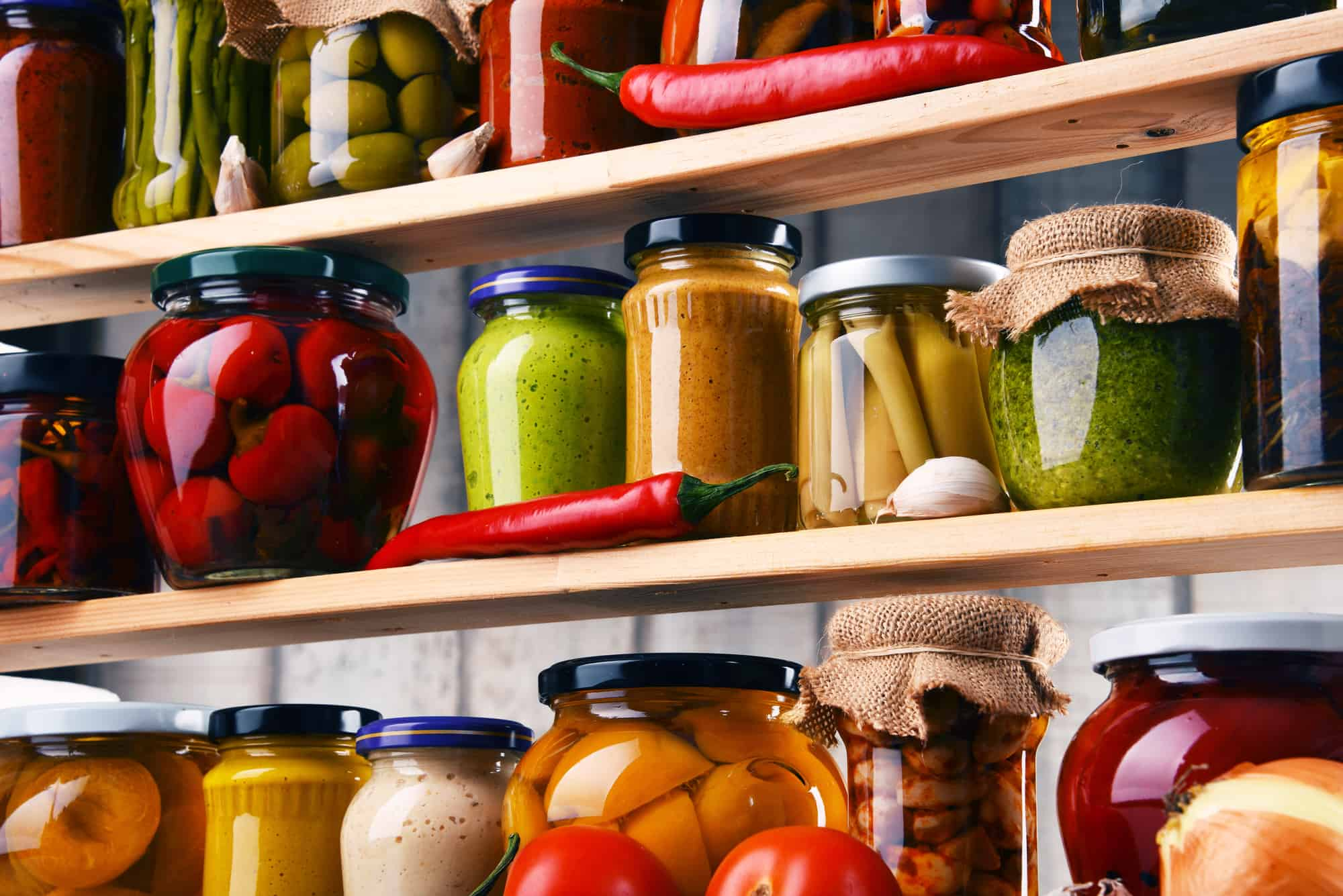 jars with variety of pickled vegetables in pantry