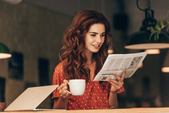 Woman with cup of coffee reading newspaper at table with laptop in cafe