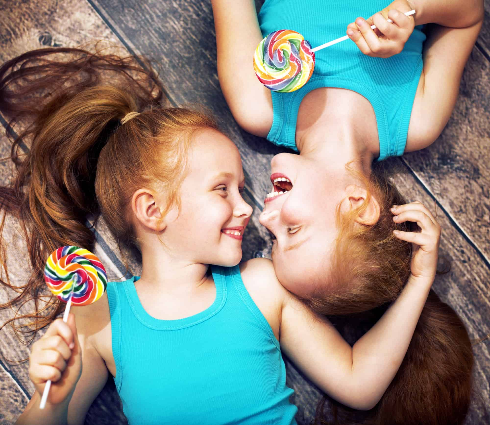 twin sisters holding colorful lollipops